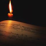 Notas musicais pela luz das velas Fotografia de Stock