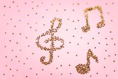 Notas musicales del confeti de oro estrellado que miente en un fondo en colores pastel rosado Fotos de archivo