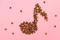 Notas musicales del confeti de oro estrellado que miente en un fondo en colores pastel rosado Imágenes de archivo libres de regalías