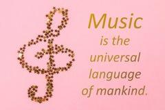 Notas musicales del confeti de oro estrellado que miente en un pastel rosado b Fotos de archivo libres de regalías