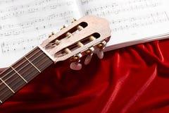 Notas na tela vermelha de veludo, ideia próxima da guitarra acústica e da música dos objetos Fotos de Stock Royalty Free