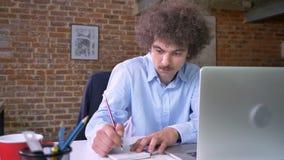 Notas nerdy jovenes del ordenador portátil, sentada de la escritura del hombre de negocios en oficina moderna, serio y concentrad almacen de metraje de vídeo
