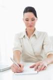 Notas novas bonitas da escrita da mulher de negócios pelo portátil Foto de Stock Royalty Free