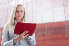 Notas novas bonitas da leitura da mulher de negócios no organizador ao estar contra o prédio de escritórios Foto de Stock