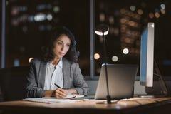 Notas novas da escrita da mulher de negócios em um escritório na noite fotos de stock