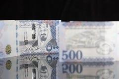 Notas novas do Riyal do saudita em uma superfície reflexiva escura Fotografia de Stock Royalty Free