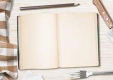 Notas o libro de cocinar en blanco de la receta con el lápiz en la tabla de cocina Imagen de archivo libre de regalías