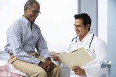 Notas pacientes masculinas de la lectura del doctor In Surgery With imagenes de archivo