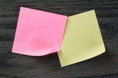 Notas pegajosas amarelas e roxas na tabela de madeira Fotos de Stock