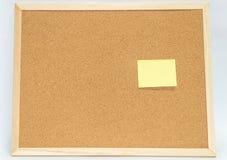 Notas pegajosas amarelas no quadro de mensagens da cortiça Imagens de Stock
