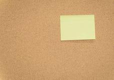 Notas pegajosas amarelas no quadro de mensagens da cortiça Foto de Stock