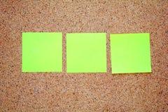 Notas pegajosas amarillas sobre un tablero del corcho Fotografía de archivo