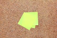 Notas pegajosas amarillas sobre un tablero del corcho Fotos de archivo