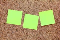 Notas pegajosas amarillas sobre un tablero del corcho Fotos de archivo libres de regalías