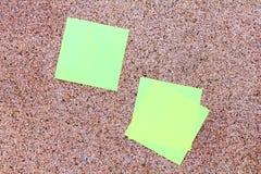 Notas pegajosas amarillas sobre un tablero del corcho Imagen de archivo