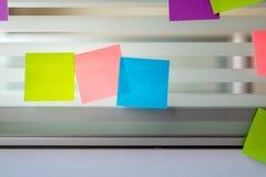 Notas pegajosas coloreadas aleatoriamente dispersadas sobre la pantalla de cristal de un escritorio del banco Fotografía de archivo libre de regalías