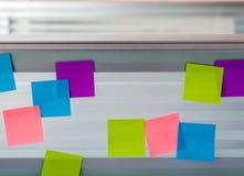 Notas pegajosas coloreadas aleatoriamente dispersadas sobre la pantalla de cristal de un escritorio del banco Imagen de archivo libre de regalías