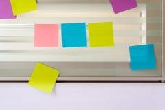 Notas pegajosas coloridas dispersadas sobre a tela de vidro de uma mesa do banco Fotografia de Stock