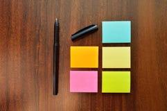Notas pegajosas coloridas e uma pena em uma tabela Imagem de Stock