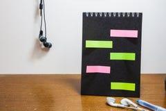Notas pegajosas coloridas no papel para cartas preto vazio Imagem de Stock Royalty Free
