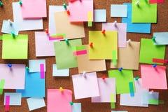 Notas pegajosas coloridas sobre tablón de anuncios del corcho Imagen de archivo