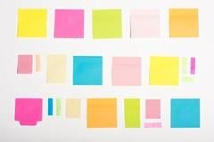 Notas pegajosas coloridas vazias diferentes isoladas no branco Imagem de Stock