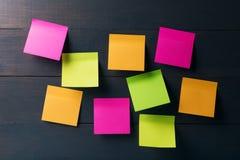 Notas pegajosas coloridas vazias no fundo de madeira Fotografia de Stock