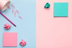 Notas pegajosas con las bolas de papel desmenuzadas en fondo en colores pastel Fotografía de archivo libre de regalías