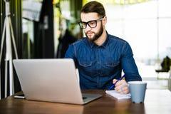 Notas que toman ocupadas del estudiante abajo de su nuevo ordenador portátil mientras que hojea Internet con su café de la mañana Fotografía de archivo libre de regalías
