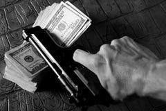 Notas y arma, pistola negra del dólar fotos de archivo libres de regalías