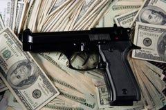 Notas y arma, pistola negra del dólar foto de archivo