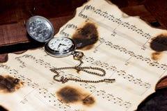 Notas y relojes Imagenes de archivo