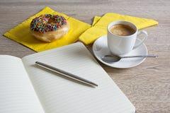 Notastootkussen met koffie en doughnut stock afbeeldingen