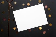 Notatka, kartka z pozdrowieniami, złoci confetti lub tasiemkowy łęk na czarnego pudełka tle, fotografia royalty free
