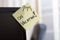 Notatka na monitorze z tekstem Na wakacje! Obrazy Stock