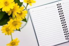 Notatka umieszczająca na białym tle z wazą żółci kwiaty Obrazy Stock