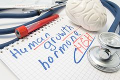 Notatka wpisująca z Ludzkim Wzrostowym hormonem HGH lub Somatotropin otacza laborancką próbną tubką z krwią, móżdżkowa postać i Obrazy Royalty Free