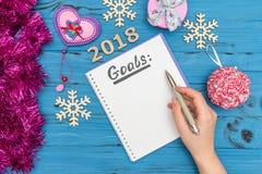 Notatnik above z celami teksty i kobiety ` s ręki mienia pióro z liczbami 2018 i nowy rok ornamentami Obrazy Royalty Free