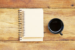 Notatnik i czarna kawa w czarnej filiżance na drewnianym stole Zdjęcia Royalty Free