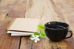 Notatnik i czarna kawa w czarnej filiżance na drewnianym stole Zdjęcie Royalty Free