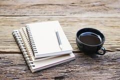 Notatnik i czarna kawa w czarnej filiżance na drewnianym stole Obrazy Stock