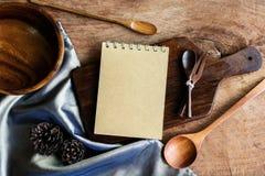 Notatnik i drewniany naczynie w kuchni na starym drewnianym tle Obrazy Stock