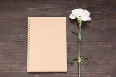 Notatnik i goździka kwiat jesteśmy na drewnianym tle Zdjęcie Stock