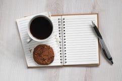 Notatnik i kawa z ciastkiem obraz stock