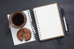 Notatnik i kawa z ciastkiem zdjęcia stock