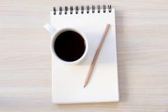 Notatnik, kawa i pióro na drewnianym stole, zdjęcie stock