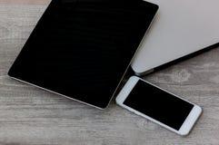 Notatnik, laptop, smartphone i pastylka ustawiający na drewnianym tle, obraz royalty free