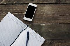 Notatnik, ołówek i telefon na starym drewnianym biurku, Prosty workspace Zdjęcie Stock