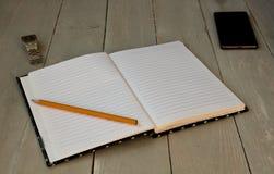 Notatnik, ołówek i zegarek dzwonimy na popielatym drewnianym bacground Fotografia Stock