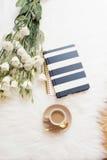 Notatnik, pastylka, filiżanka kawy i wielkiego bukieta biali kwiaty na podłoga na białym futerkowym dywanie, Freelance mody comfo Zdjęcie Royalty Free